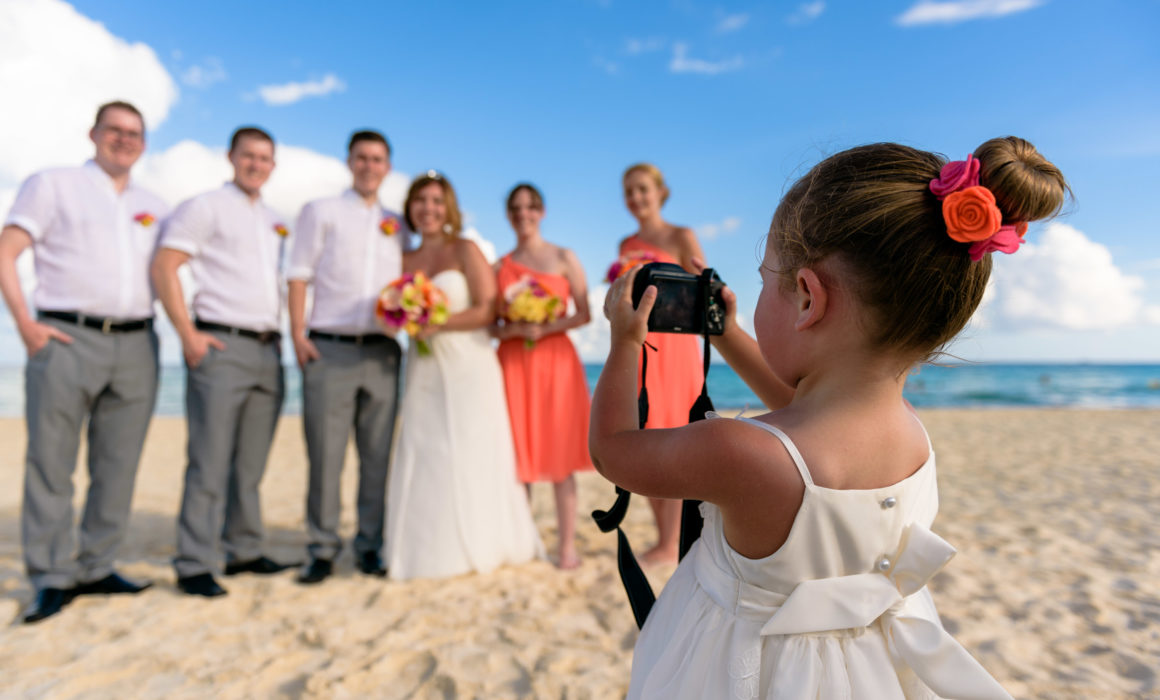flower girl taking picture of the wedding party